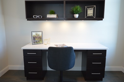 dark office desk with wall shelf above