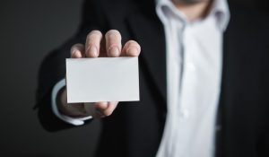 closeup of man holding a business card