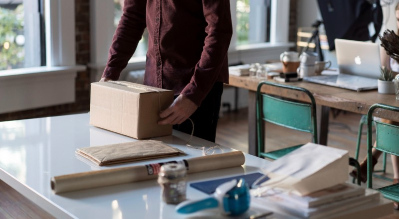 man in office preparing box for shipping